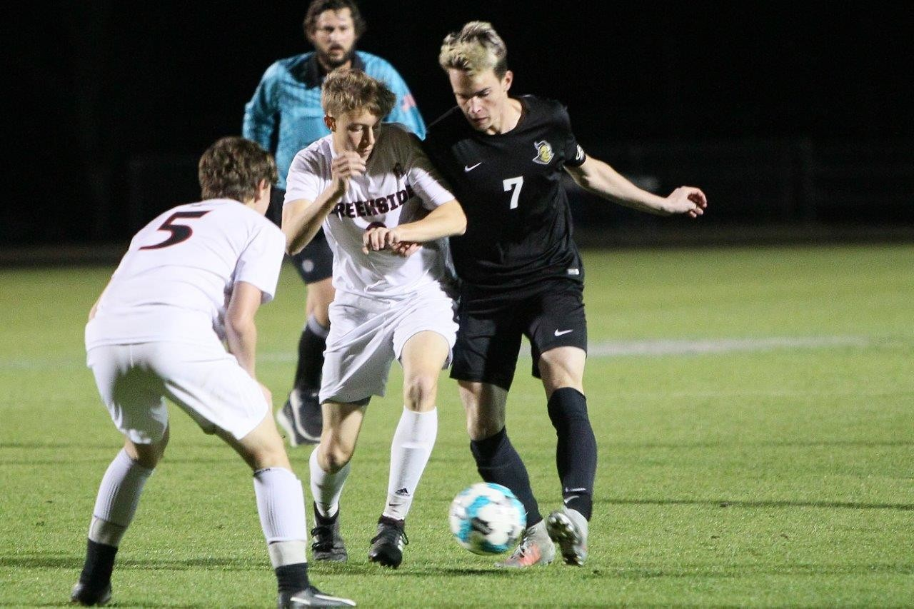Oakleaf's Andrew Henderson, No. 7, battles for ball with Creekside defender.