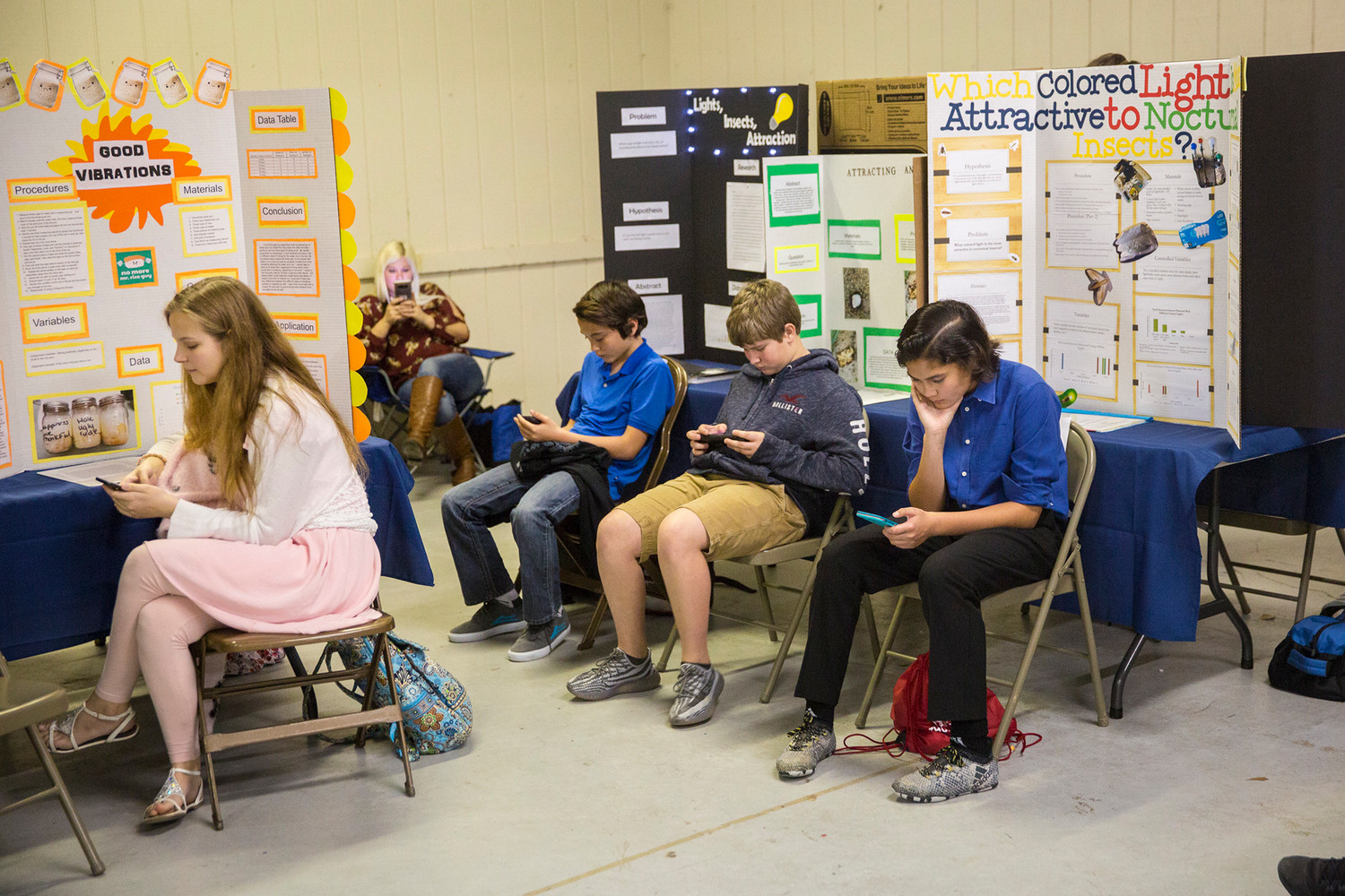 Students take to their phones during a break in judging Tuesday morning during the Clay Rotary Science Fair at the county fairgrounds.