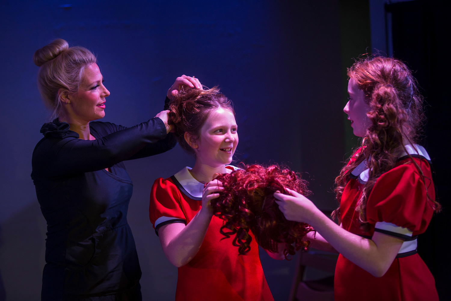 Tammy Jones, left, helps her daughter Annabel Jones, 10, center, with her hair while the younger Jones gets help with her wig from co-Annie Autumn Henry, 11, before the opening night of the Island Theater's production of Annie the Musical.