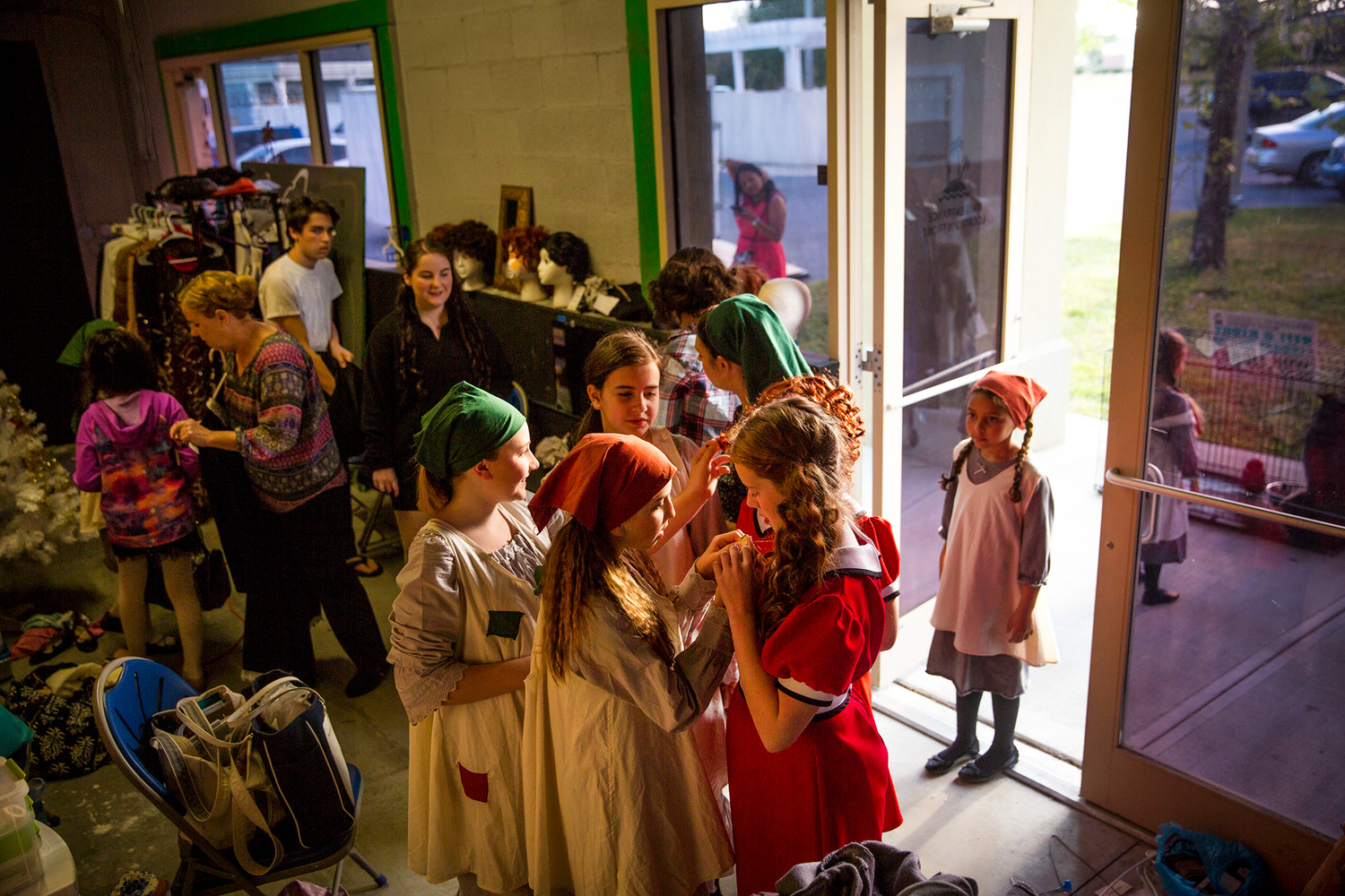 Various orphans help each other get costumes ready before showtime Friday evening at the Island Theater before their first ever performance of Annie, their first show ever.