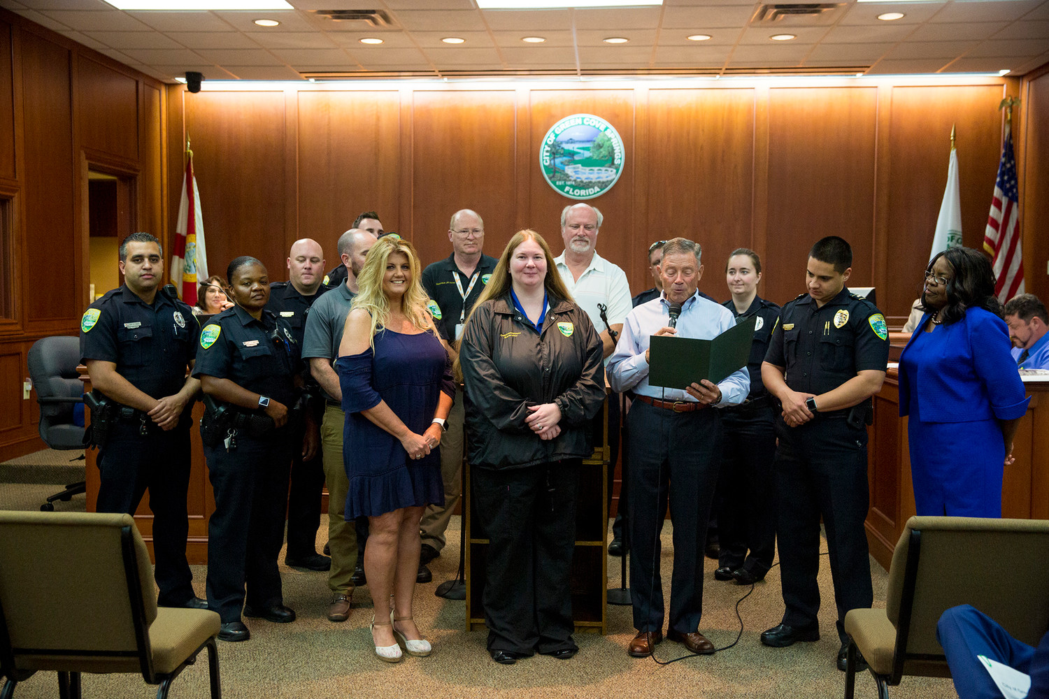 Green Cove Springs Mayor Mitch Timberlake reads a Proclamation Tuesday evening in honor of National Public Safety Telecommunicators Week.  Several officers from the Green Cove Police Department showed their support by standing up with Communications Officer Sharon Adamson, left center, and the department's supervisor Brandi Acres, center, who have both worked every day for eight months while the department looked to hire additional dispatchers. Timberlake noted at the end that despite the women's round-the-clock shifts, they are still able to keep response times at between three and four minutes compared to the 45 minutes of the Clay County Sheriff's Office.