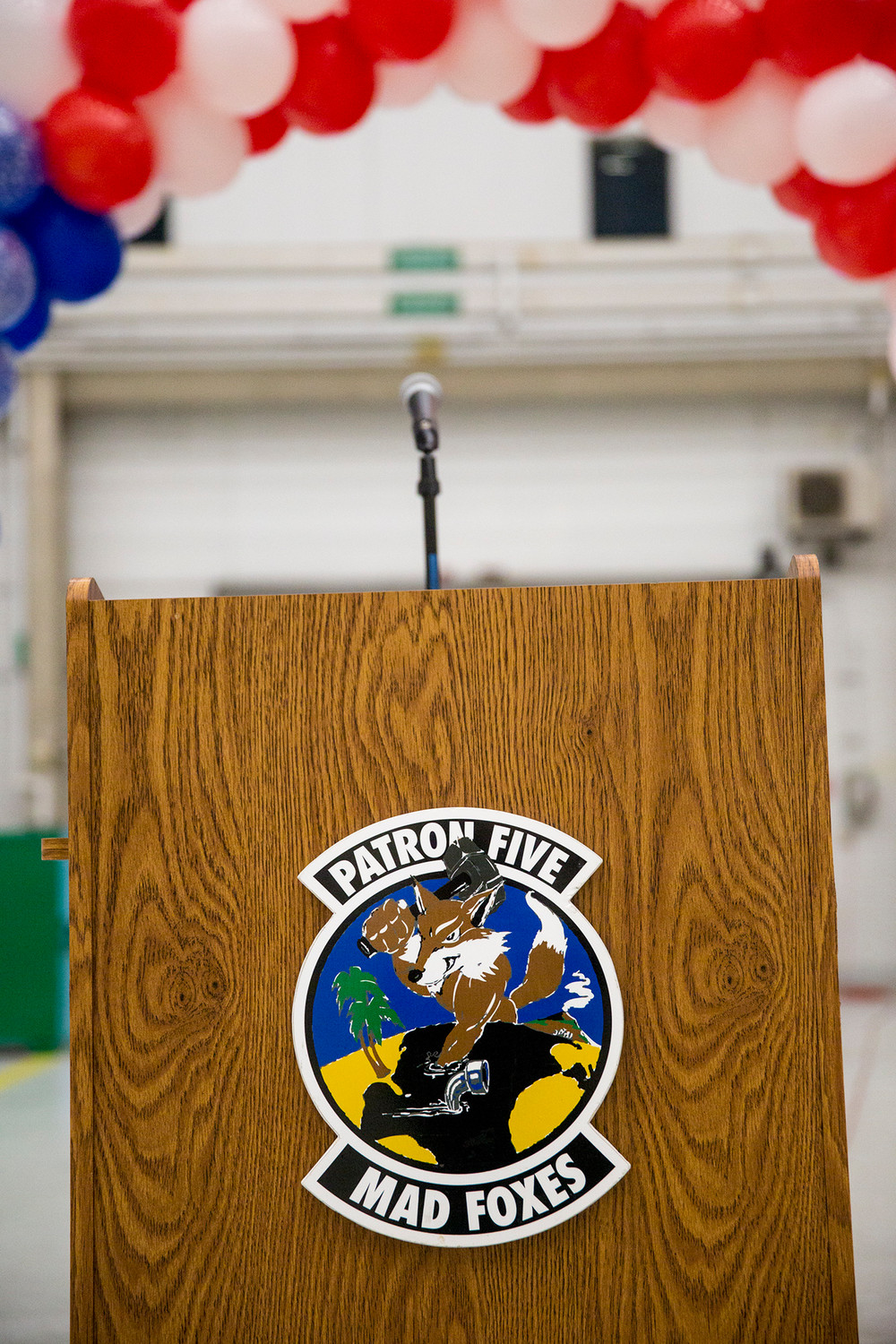 A podium marked with the VP-5 Mad Foxes emblem sits ready for Commanding Officer Will Toraason Tuesday as the remaining members of VP-5 returned to Naval Air Station Jacksonville.