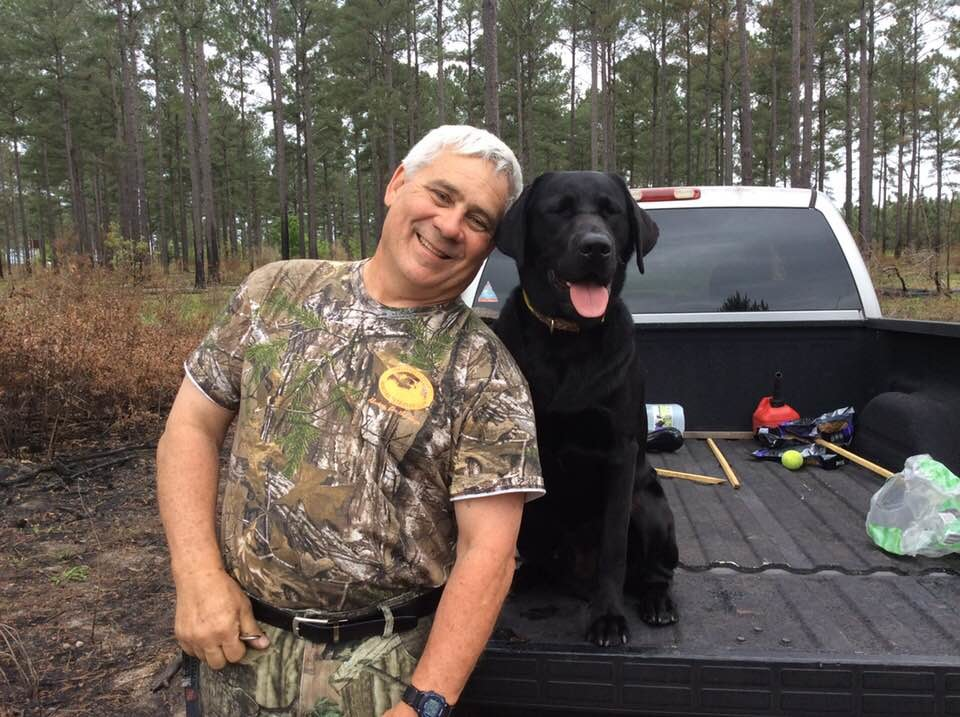 Mike Davis, left, smiles with his dog SHR Maximus Aurelis Davis after the Davis earned four ribbons in two days to get Max a Hunt Retriever title. Max is a one year old Black Labrador.