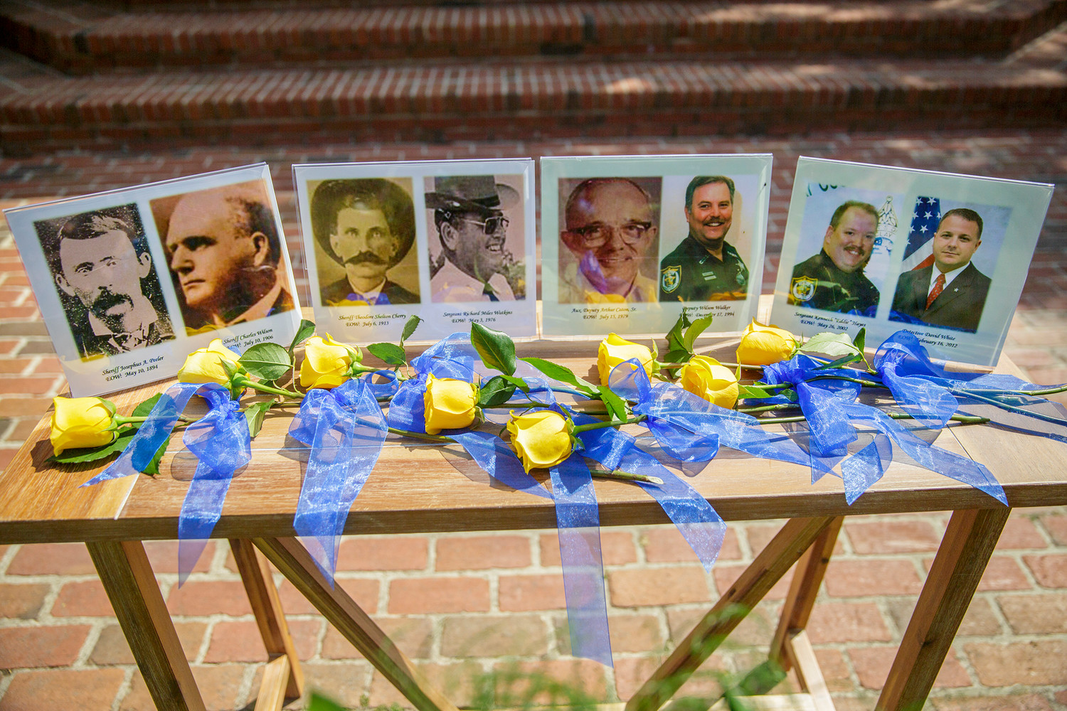 Photographs of the eight fallen officers from the Clay County Sheriff's Office sit next to their accompanying yellow roses Tuesday following the ceremonies at this year's Police Memorial Service.
