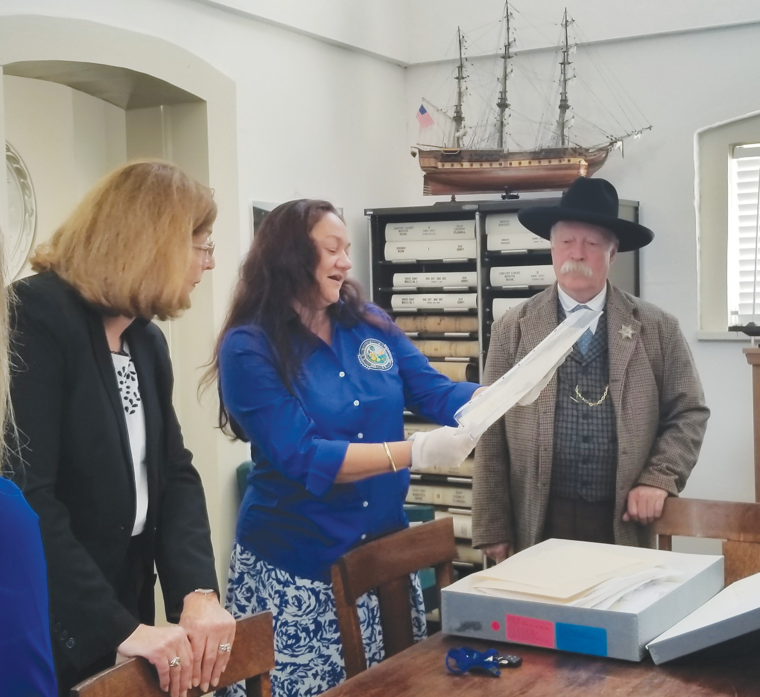 While wearing protective gloves, Clay County Archivist Vishi Garig, in center, reads from a Clay County historical document May 26, while Clay County School Board Chairman Carol Studdard looks on from left. At right, Joseph Lorentzen is dressed in period garb as he portrays one of Clay County's sheriffs.