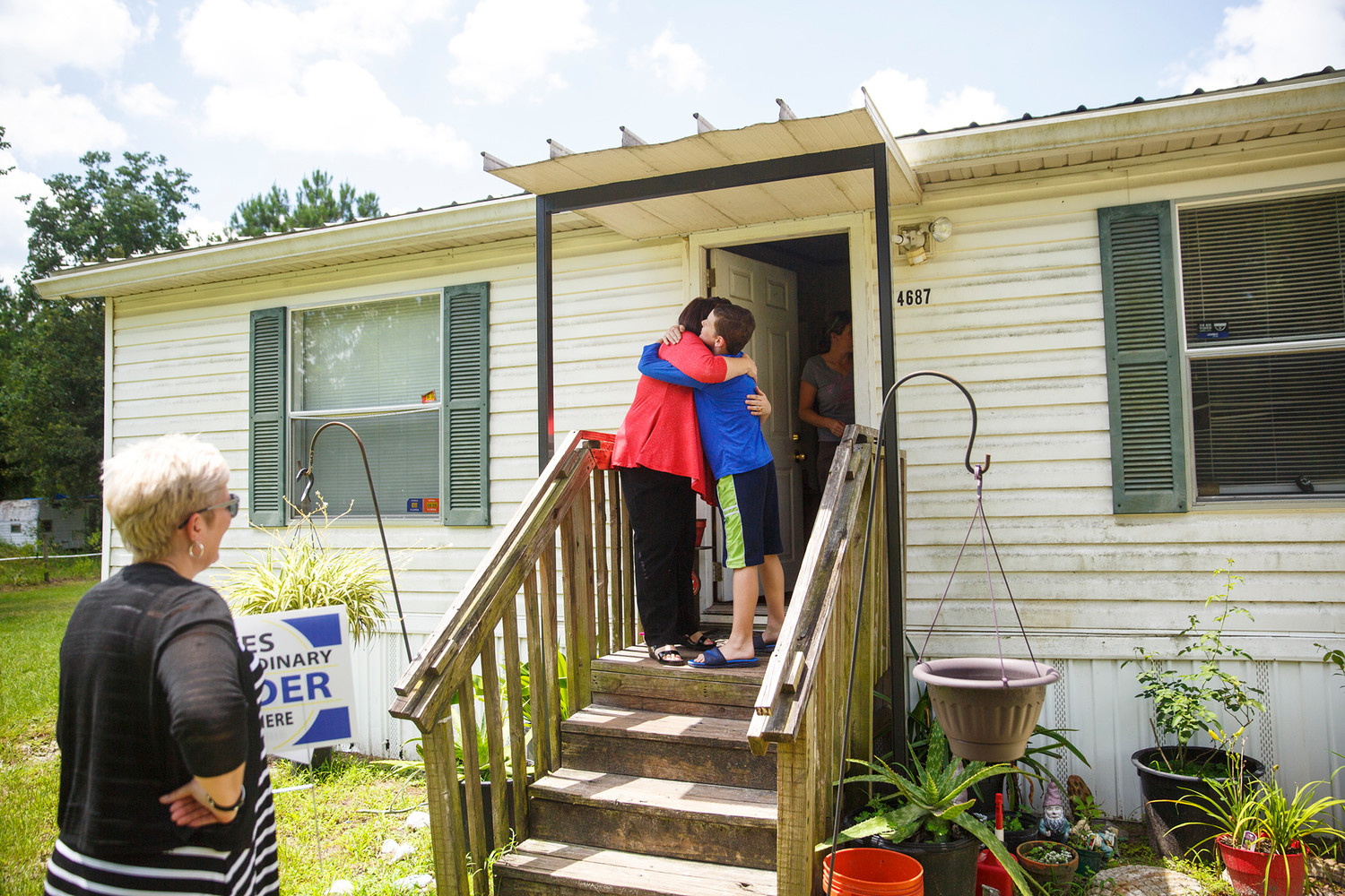 Wilkinson Elementary School Principal Heather Teto, right, hugs student Jessie Kelley Jr.,10, Monday when Teto and the school's assistant principal Carolyn Hayward delivered a sign to Kelley's house identifying him as one of the school's top readers coming out of fourth grade.
