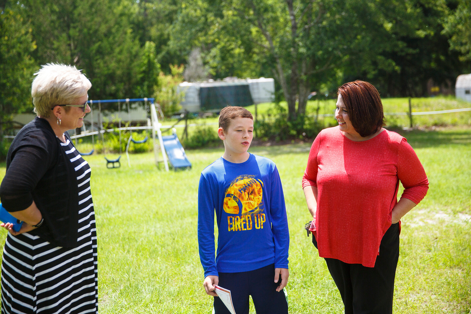 Wilkinson Elementary School Assistant Principal Carolyn Hayward, left, and Principal Heather Teto, right, talk with Jessie Kelley Jr., 10, Monday after visiting him at home to deliver a sign identifying him as one of the two top readers in the fourth grade class.