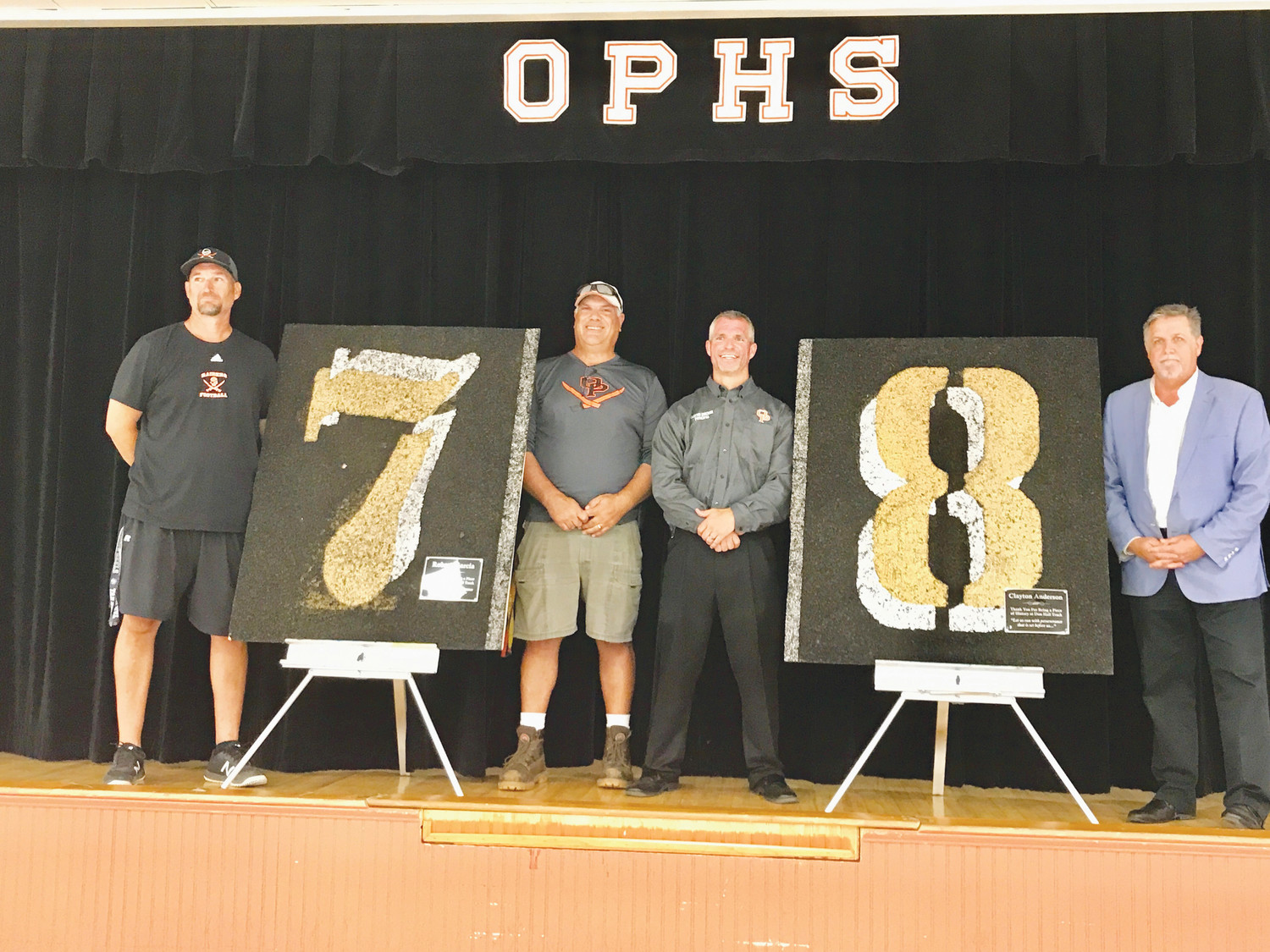 From left, Michael Harrison, Rob Garcia, Clayton Anderson and Michael Wingate recently took part in a ceremony where school officials presented legendary track coach Don Hall with a piece of the rubber track that is being replaced with asphalt.