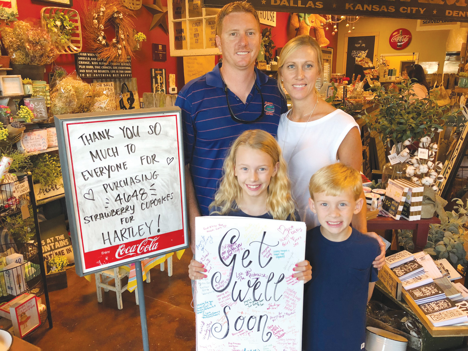 Matt, Michelle, Hartley and Carter Georges stand in front of the sign noting the amount of cupcakes sold. The family said they were grateful for the community outreach following Hartley's two surgeries.