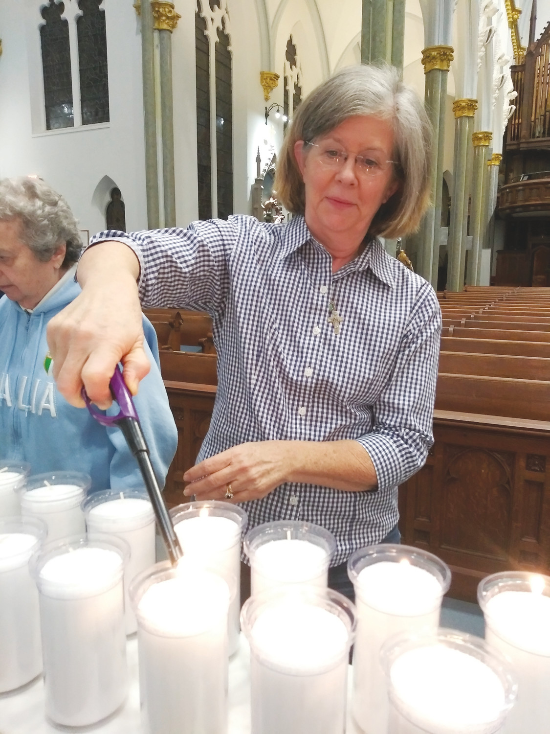 St. Catherine's Catholic Church parishioner, Martha Malone of Ortega, lights a candle Nov. 30 at the Basilica of the Immaculate Conception as part of the Cities of Light event to raise awareness about abolishing the death penalty.