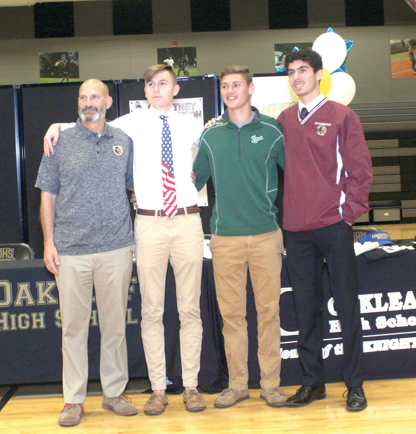 Oakleaf High soccer coach Fred Hulett, left, stands with three of his athletes; l-r, Tim Morgan, Braden Ammon and Vito Fasulo prior to the trio signing to play college soccer.  Morgan will play at Brewton-Parker in Georgia. Ammon will play at University of South Florida. Fasulo will play at the University of South Carolina-Salkehatchie. Not pictured was Jared McGregor who will play at LaGrange College.