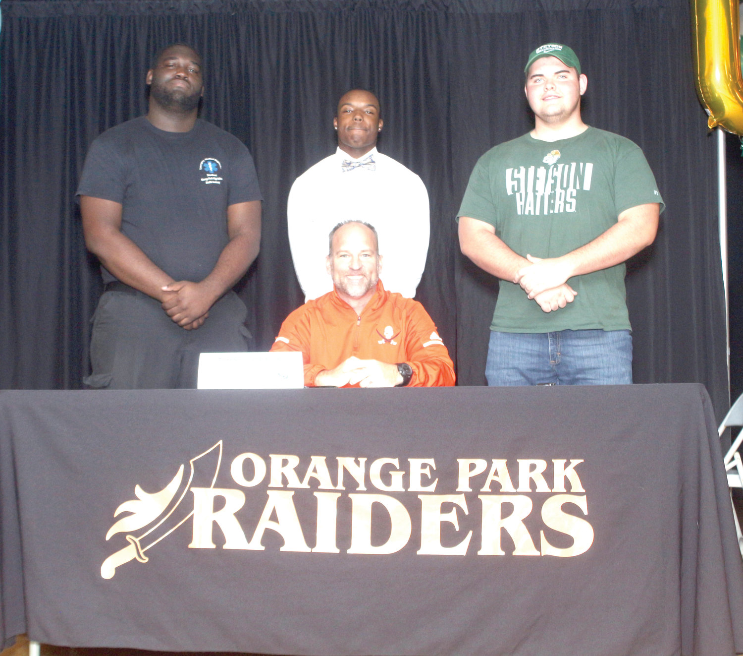 Orange Park footbal coach Tom Macpherson, seated, signed off three players; l-r, Cedrick Flanders, offensive line to Hutchinson Community College in Kansas; Terrance Johnson, offensive weapon, to Dodge City Community College in Kansas, and James Rhodes, offensive line, to Stetson University.