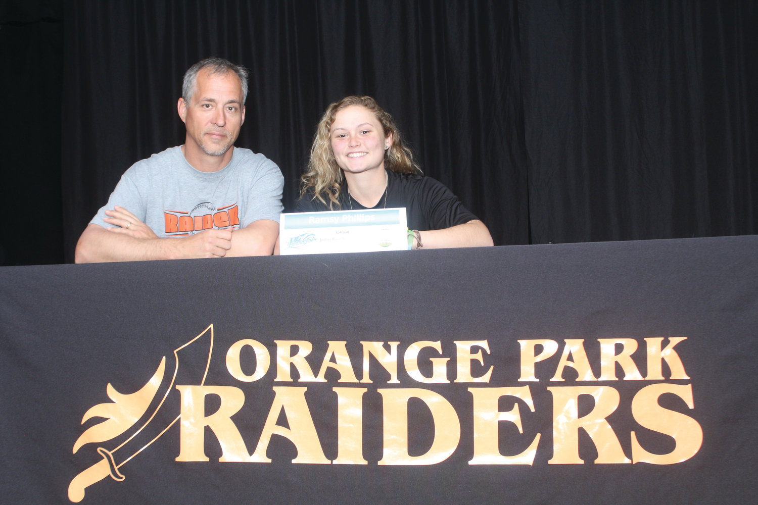 Orange Park High softball coach Lee Taylor, left, sits with Ramsy Phillips, an softball infielder who signed to play at Indian River State College in south Florida.