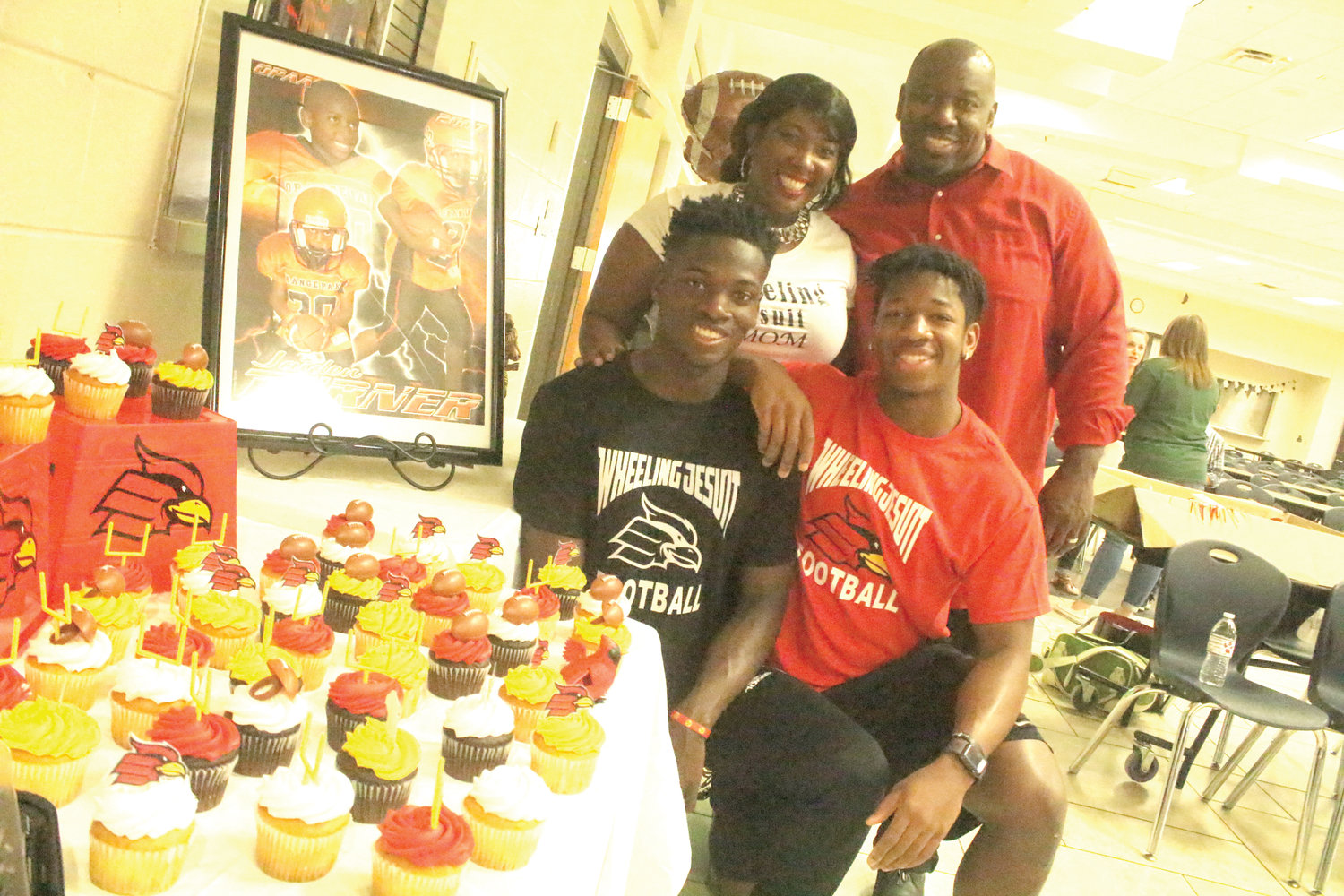 The Turner family, mom Daphne, and dad Terrance, check out signing ceremony cupcakes with sons Jaiden, left, and Kiaran as Jaiden was signing to join his older brother at Wheeling Jesuit University to play college football.
