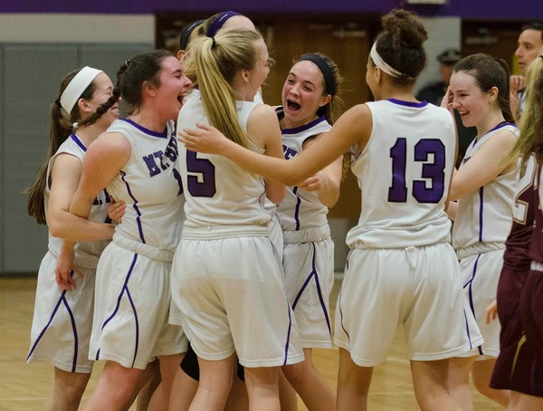 The Lady Huskies celebrate after beating Tiverton 39-28.