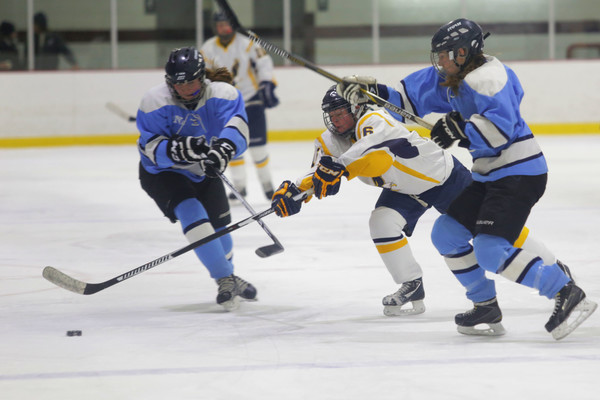 East Bay captain Grace Flaherty tries to steal the puck from a pair of South County players.