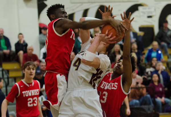 East Providence defenders David Ogunronbi (middle) and Dion Hazard (right) thwart Tiverton's Steve Gacioch as he drives towards the hoop.