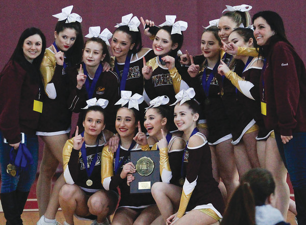 Tiverton High School cheerleaders and Coach Susan McDermott pose with their medals and Small School Division state championship plaque Saturday.