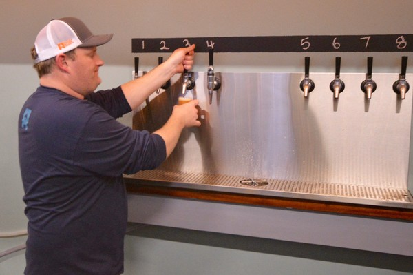 Matt Gray pours an Indivisible Double IPA for a customer.
