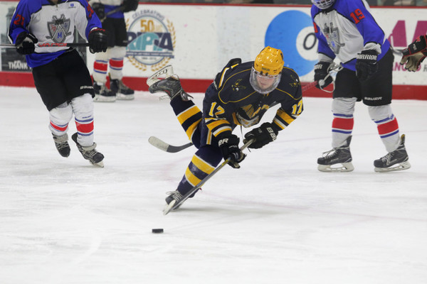 Senior Kyle Shuman dives for the puck in front of the RMR goal.