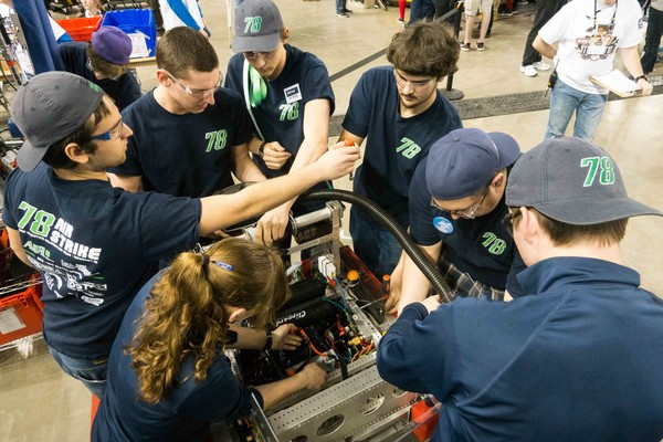 Members of Team AIR STRIKE 78 tinker with their robot during a recent competition.