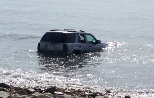 A car sits in the ocean after rolling into the unusually calm water from the beach parking lot last Wednesday. (Little Compton Fire Department photo)