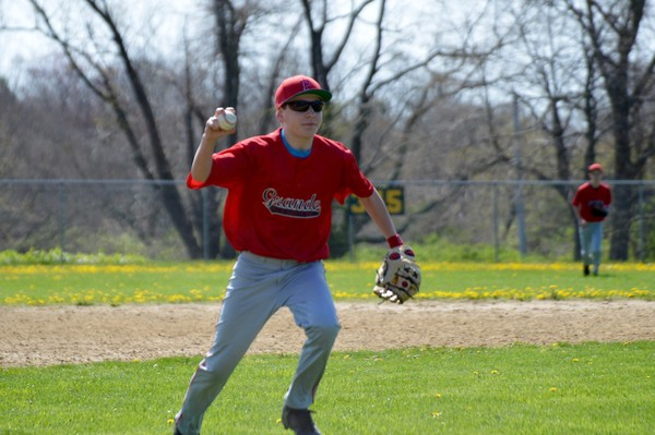 Grande Masonry third baseman Zach Sherman looks to throw to home plate against R&R Construction.