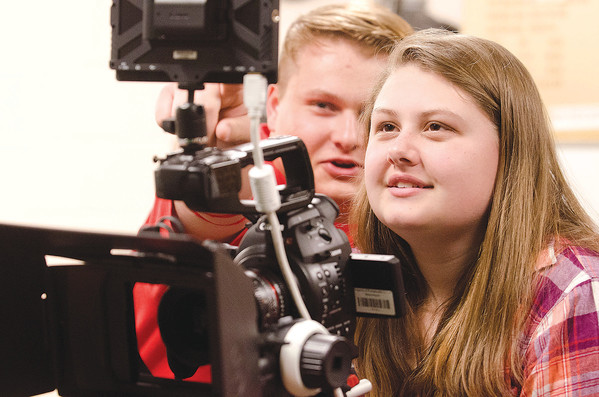 Portsmouth High senior Leah Paulon runs a camera on a platform dolly unit as director Jake Vaspol looks on during a shoot in the school's media room on Friday.