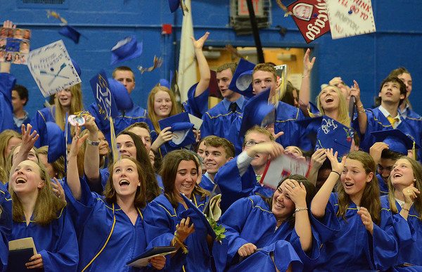 From left, Paige Greenberg, Lindsay Daugherty, Lily Gagliano, Bella Campanini, and their classmates heave their caps into the air after commencement inside the high school gymnasium on Sunday afternoon.