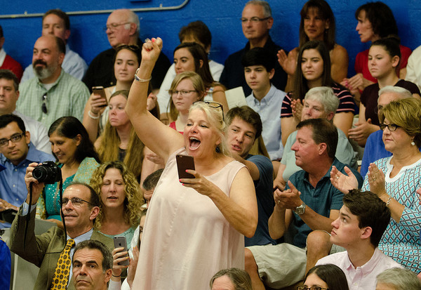 A mom cheers on her graduate during commencement.