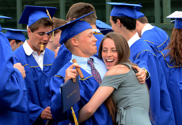 Tommy Murray gets a hug from girlfriend, Kayla Howarth in the courtyard after graduation.