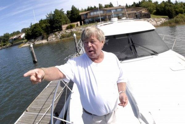 Don Kidd points out towards a sunken wreck south of his dock and his boat that is now shedding boat parts.