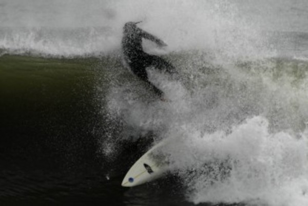 A surfer prepares for a pounding off Little Compton last fall.