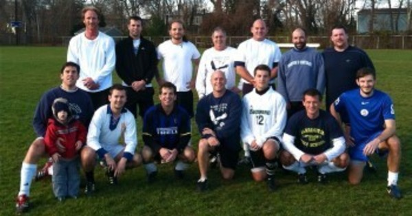 Players (and young fan Colin Pickering) pose at the end of the 29th annual Barrington High School alumni soccer game.