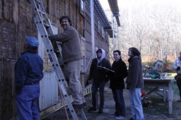 Architectural historian Eric Gradoia, on the ladder, explains to architectural students from Roger Williams University what the markings found on the side of Handy House might mean. Also taking a close look (left) last Tursday is Ted Kinnari, a member of the Westport Historical Commission.