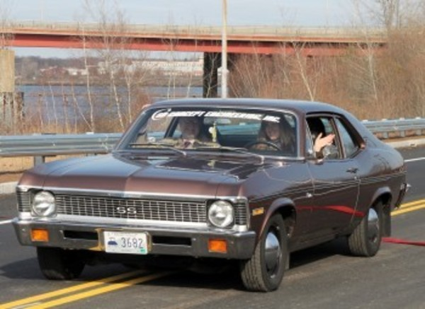 Wendy Dickinson, co-owner of SD Concepts, drives a classic Chevy Nova along Waterfront Driver during Friday's ribbon-cutting ceremony for the span. Mrs. Dickinson is bring her business to East Providence from West Warwick.