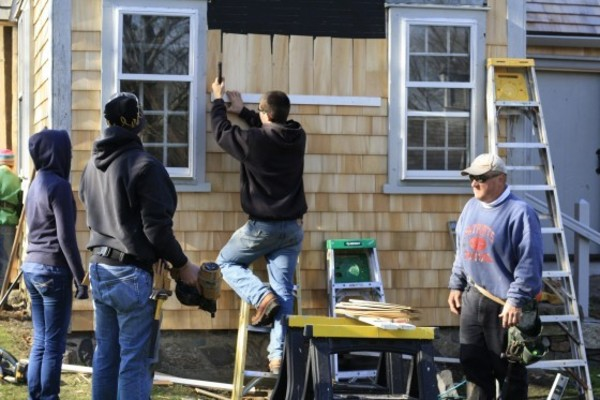 In re-shingling project, William Phillips, technical education teacher (right), works alongside students Ryan Mirka (on ladder), Zach Silveira, and Hannah Cook-Dumas (left).