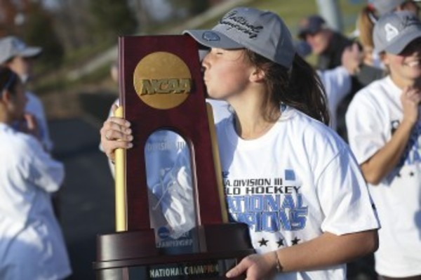 Kelsey Perkins (8) of Tufts University kisses the champioship trophy after the Division III Women's Field Hockey Championship held at J.J. McCooey Memorial Field in Geneva, NY. Tufts defeated Montclair State 2-1 to win the national title. Kevin Colton/NCAA Photos