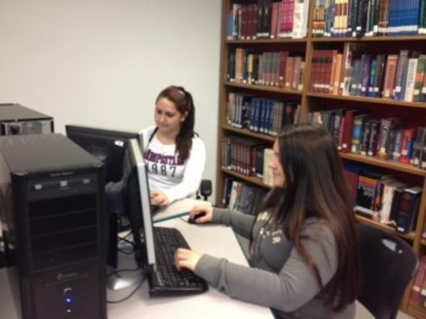 Taylor Soares and Heather Miranda work with the new computer program.