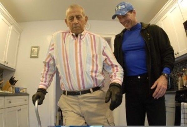 After being confined to a wheelchair for 13 years, Bill Iacovelli takes a few steps through his kitchen while personal trainer Glenn Brown looks on.