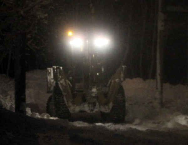A backhoe clears out a side street in East Providence at nightfall Saturday, Feb. 9.