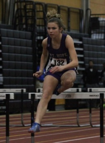 Kylie McPherson of Mt. Hope glides over a hurdle at the indoor track State Championship Meet.