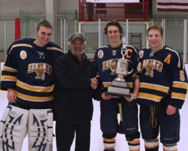 JP Medeiros, shown during a recent hockey tournament with members of the high school team, will retire at the end of the school year.