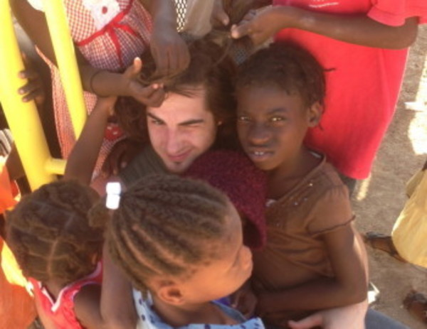 Barrington's JR Martin is hugged by children during the recent Rhode Trip mission work in Haiti.