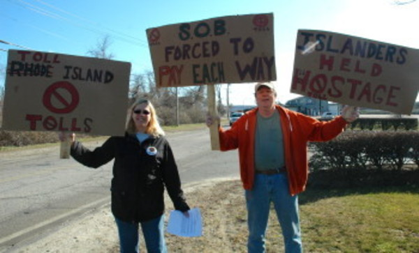 "Cheryl and Randy Martin wave signs at cars outside the Roger Williams University Conference Center before Saturday's workshop. The only business that will increase as a result of the sales, said Mr. Martin, would be the sales of plywood ""to board up all the businesses that will be shut down."""