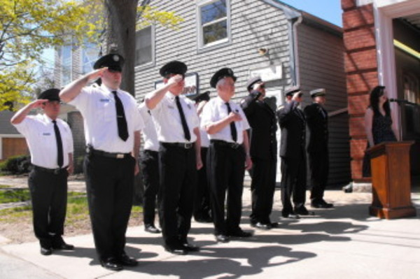 Members of Dreadnaught Fire Company stand at attention as Victoria Carroll sings the National Anthem at the station's flagpole dedication on Sunday, April 28, 2013.