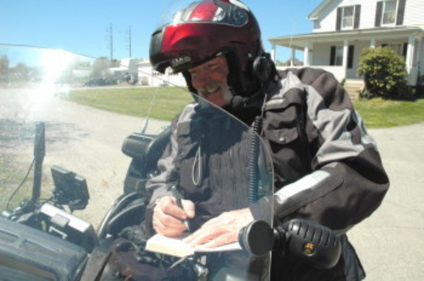 Bruce Garry records some notes outside Founder's Grove before hitting the road again on Saturday. Mr. Garry has logged about 3,000 miles on his motorcycle to raise money for the Wounded Warrior Project.