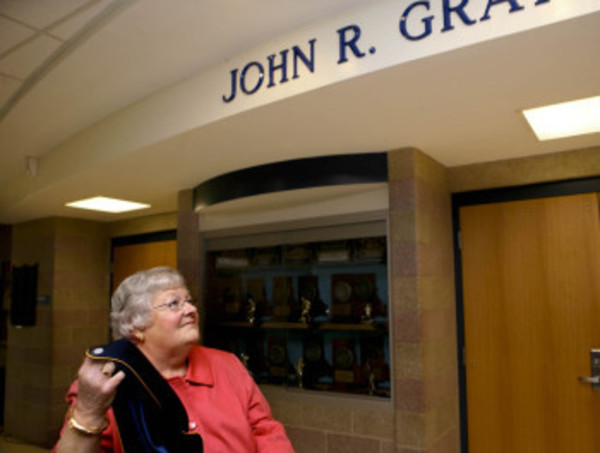 Cheryl Gray, wife of John Gray, long-time Barrington High School Principal who passed away last year, unveils the sinage at the enterance to the school's auditorium, as the room was named in Mr. Gray's honor, Saturday. Photo by Bill Murphy