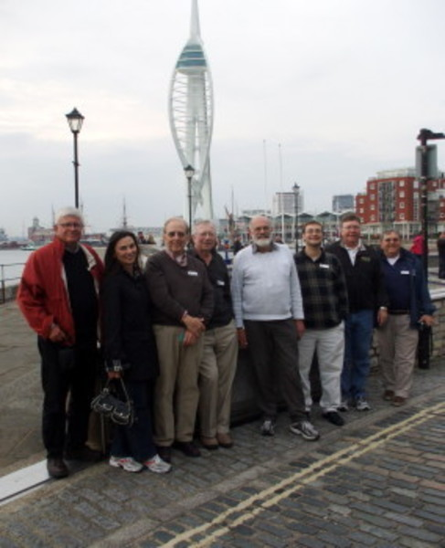 Portsmouth (England) City Council member Hugh Mason (center, with light-gray sweater) gave the local delegation a walking tour of the old section of the city on Saturday. From left are Doug Smith, chairman of the Portsmouth 375th Steering Committee; Town Council member Elizabeth Pedro; Gary Gump and Bob Hamilton of the steering committee; Mr. Mason; School Committee member Andrew Kelly; Town Administrator John Klimm; and Rich Talipsky of the steering committee. Portsmouth Harbour's 560-foot Spinnaker Tower is in the background.
