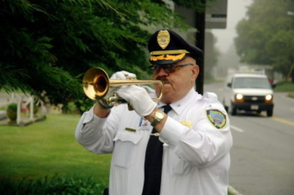 "Arthur Caesar, a bugler with the Marine Corps League honor guard, plays ""Taps"" at Legion Park in front of Town Hall Friday."